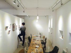 어반플루토 갤러리 크리스마스 일러스트 그룹 전시회 작품을 벽에 거는 중