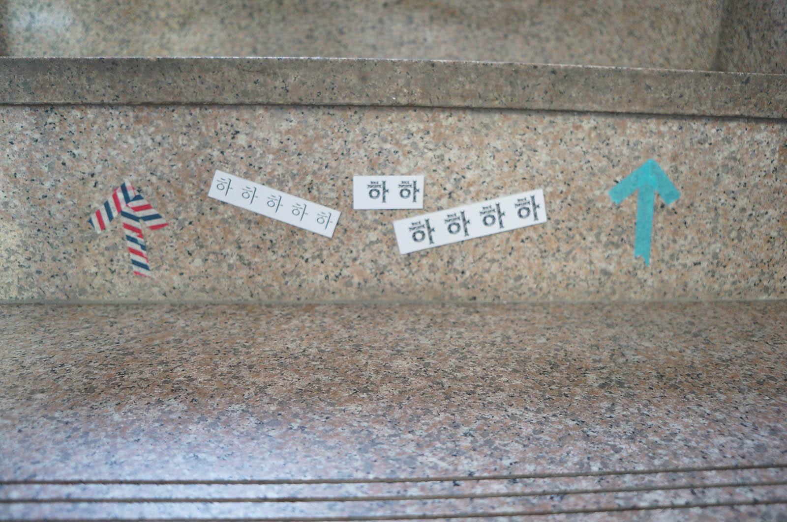 어반플루토 갤러리 2층 올라오는 계단에 부착된 화살표와 하하하 문구